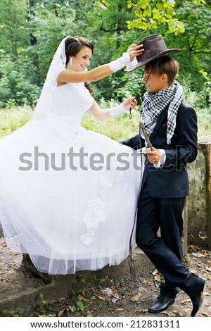 the bride wears a cowboy hat groom - stock photo