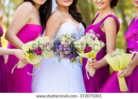 the bride with a bouquet and bridesmaids in lilac dresses - stock photo