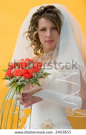 The bride with a bouquet of roses on a yellow background - stock photo