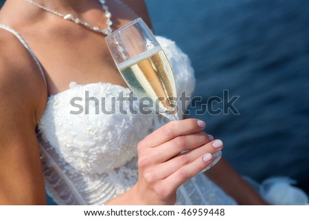 The bride with a glass of champagne during river voyage - stock photo