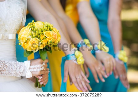 the bride with a yellow bouquet of roses and bridesmaids in blue and yellow dresses - stock photo