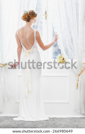 The Bride / Young women with wedding dress in very bright room, some fine film noise effect added
