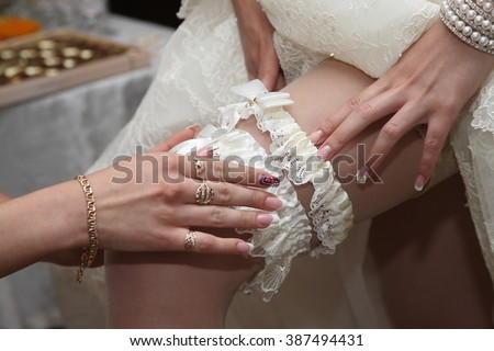 the bridesmaid helps to wear a wedding garter