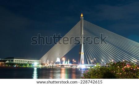 The bridge across the river at night, Rama VIII bridge, Bangkok, Thailand - stock photo