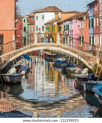 The bridge and the colored houses on the shore of a narrow channel - Burano, Venice, Italy - stock photo
