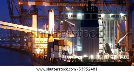 The bridge of a big container ship being loaded at dusk at an industrial harbor - stock photo