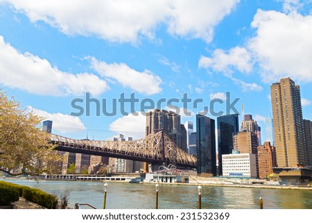 The bridge to Roosevelt Island during cherry blossom in New York City. A view on Manhattan from the East River in spring. - stock photo