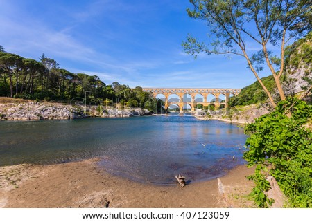 The bridge was built in Roman times on the river Gardon. Three-tiered aqueduct Pont du Gard - the highest in Europe. Provence, spring sunny day - stock photo