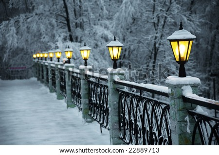 The bridge with beautiful lanterns, the fine snow evening in mountains - stock photo