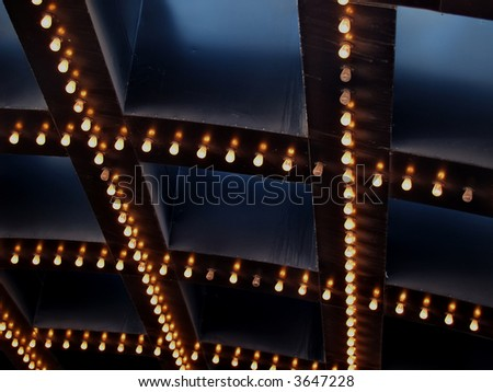 The bright lights of a theatre marquee in a downtown city - stock photo
