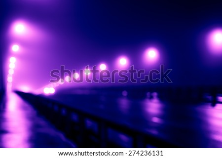 The bright lights of the city at night, the headlights of the approaching car on the road bridge. Defocused image, image in the purple-blue toning