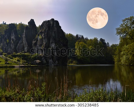 The bright moon hovers over a rock formation.