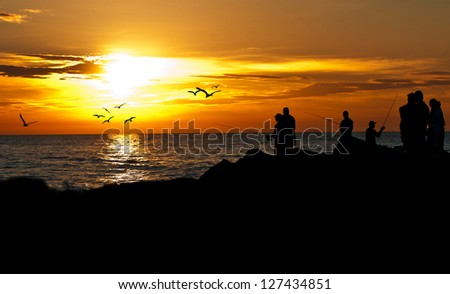 The bright orange and yellow skies of a January sunset at South Jetty in Venice Florida, as fishermen get the last catch of the day in the Gulf of Mexico waters from the rocky end of the pier. - stock photo