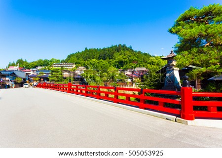 The bright red Naka-Bashi bridge marks the entrance to historic old town, a tourist destination in the mountain city of Hida-Takayama in Gifu Prefecture, Japan at daytime. Horizontal