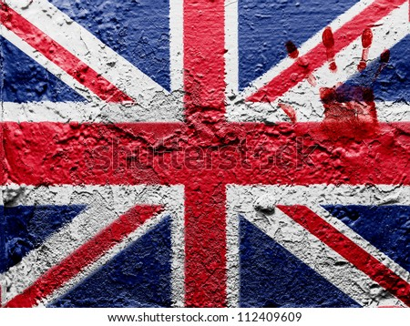 The British flag painted on grunge wall with bloody palmprint over it