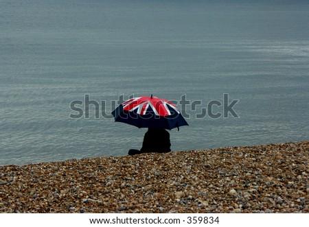 The British on Holiday - focus on umbrella - stock photo