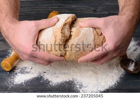 the broken bread in male hands - stock photo