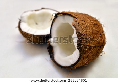 the broken fresh coconut on a white background - stock photo