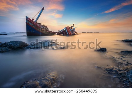 The broken ship along with the sea and sunset twilight sky - stock photo
