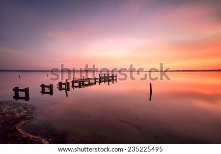 The broken timber jetty at Gorokan  on the Budgewoi Lake at bathed in glorious colours of sunrise, Central Coast Australia - stock photo