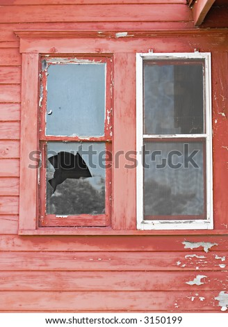 The Broken Window Of An Old Red House - stock photo