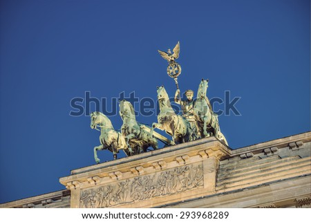 the bronze sculpture Quadriga on top of the Brandenburg Gate (Brandenburger Tor) at evening, Berlin, Germany, Europe, vintage filtered style - stock photo