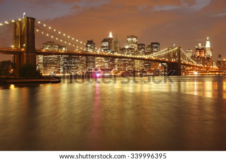 The Brooklyn Bridge and Manhattan skyline as seen from across the East River at dusk.