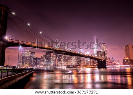 The Brooklyn bridge at night with a skyline of Manhattan in the background.