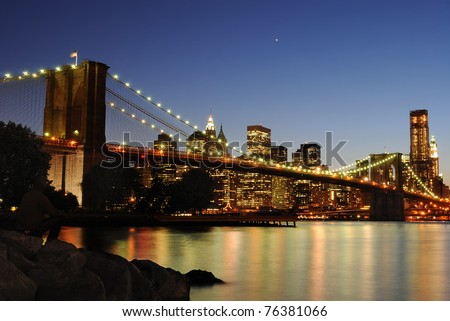 The Brooklyn Bridge illuminate at night with skyscrapers behind.