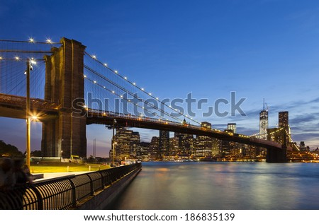 The Brooklyn Bridge in front of the Manhattan skyline in New York City at night.