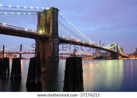 The Brooklyn Bridge spans the East River in New York City as it shimmers at night