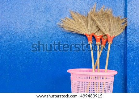the brooms made from grass flower on blue cement wall.
