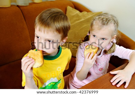 The brother and sister hold crackers and attentively watch TV