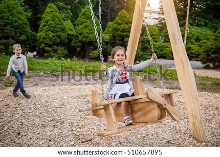 The brother rolls the younger sister on a swing. Children playing outdoors in summer.