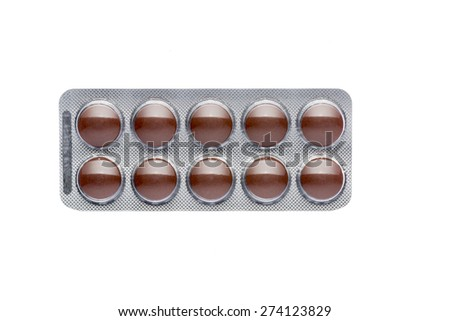 The brown pills in a blister on isolated background - stock photo
