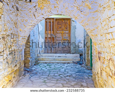 The brown wooden door behind the old arch , covered with the crumbling plaster, Lefkara, Cyprus.