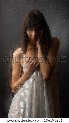 The brunette in a white dress for a wet glass on a black background.