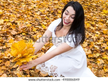 The brunette in a white dress on a background of autumn leaves