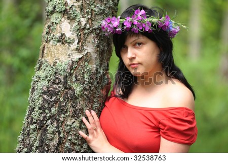 the brunette looks from behind the tree - stock photo