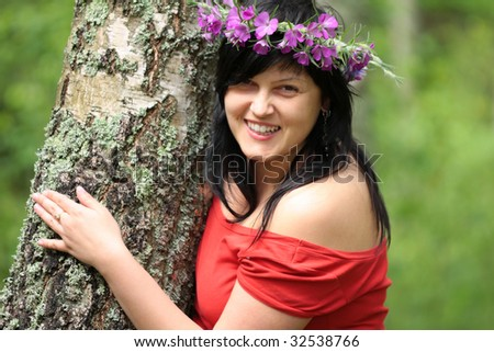 the brunette looks from behind the tree and smiles - stock photo
