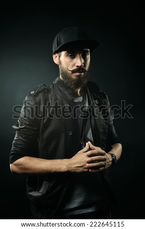 The brutal bearded man in a black jacket folded his arms in a lock - stock photo