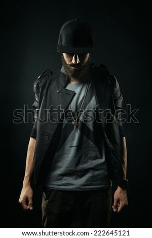 The brutal bearded man in a black jacket stands with his head bowed - stock photo