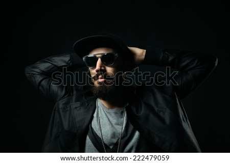 The brutal bearded man in a black sunglasses clasped his hands behind his head - stock photo