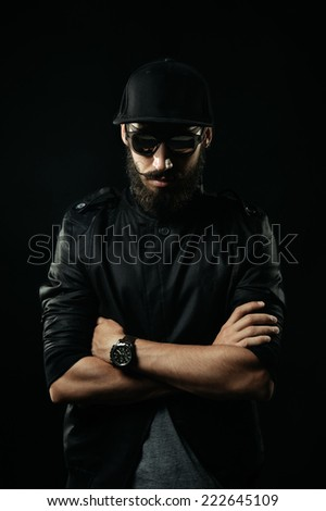The brutal bearded man with sunglasses folded his arms across his chest - stock photo