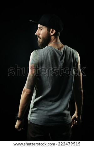 The brutal bearded man with tattoos is standing back - stock photo