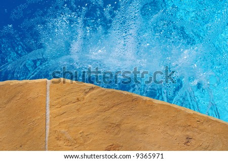 The bubbling water seen from above at the edge of a in ground pool - stock photo