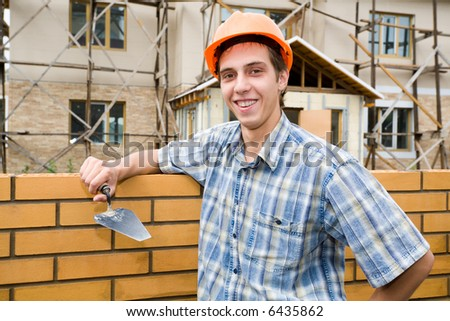 The builder erects a wall from a brick. - stock photo
