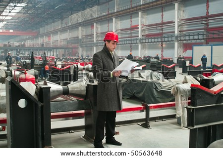 The builder in a helmet with drawings on metal works among the equipment the rolling mill - stock photo
