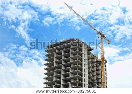 The building crane near not complete skyscraper - stock photo