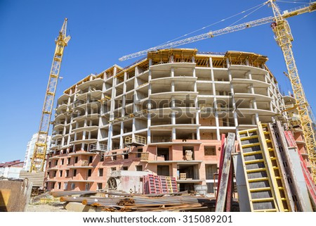 the building under construction with cranes against the blue sky - stock photo